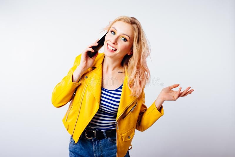 Het meisje in een helder geel jasje maakt een selfie voor sociale netwerken op smartphone stock fotografie
