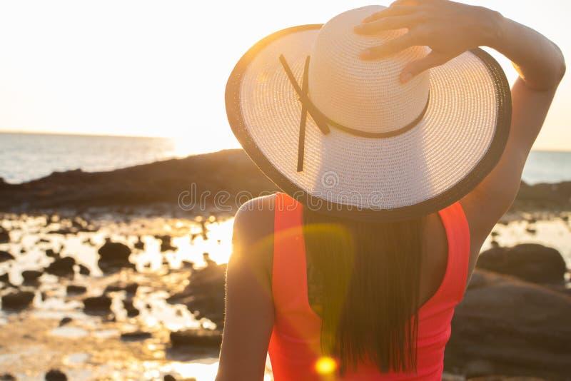 Het meisje in een hoed wandelt langs het strand bij zonsondergang royalty-vrije stock fotografie