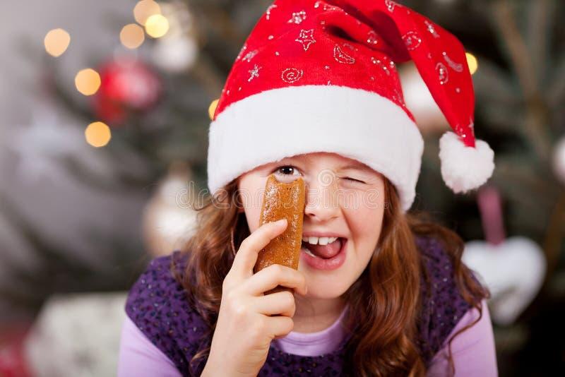 Het meisje in een Kerstmanhoed die blij geven knipoogt stock afbeeldingen