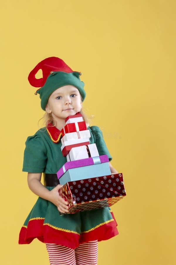 Het meisje in een kostuum van het Kerstmiself, draagt een stapel giften Foto op een gele achtergrond stock fotografie