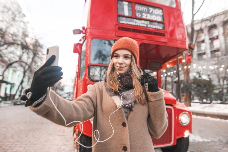 Het meisje in een laag en de hoofdtelefoons die zich in openlucht tegen een achtergrond van rode bus bevinden en nemen selfie De  royalty-vrije stock afbeelding