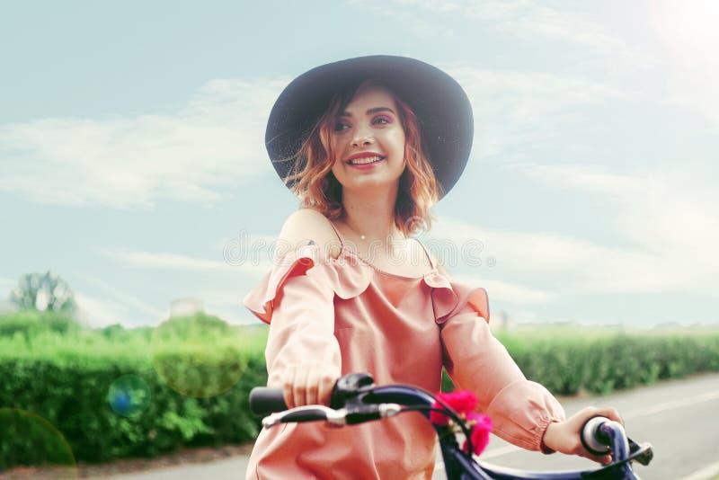Het meisje in een mooie roze kleding en een zwarte hoed berijdt een fiets royalty-vrije stock fotografie