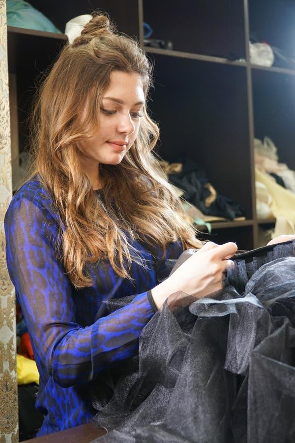 Het meisje is een naaister die in een naaiende workshop werken royalty-vrije stock afbeelding