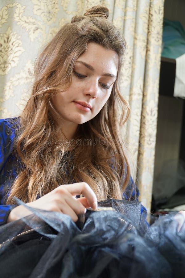 Het meisje is een naaister die in een naaiende workshop werken stock foto's