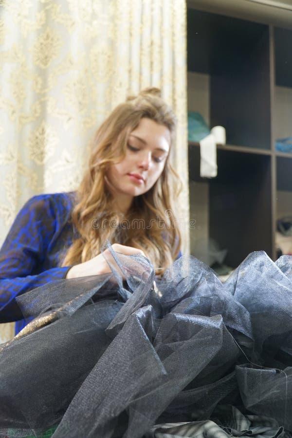 Het meisje is een naaister die in een naaiende workshop werken royalty-vrije stock foto