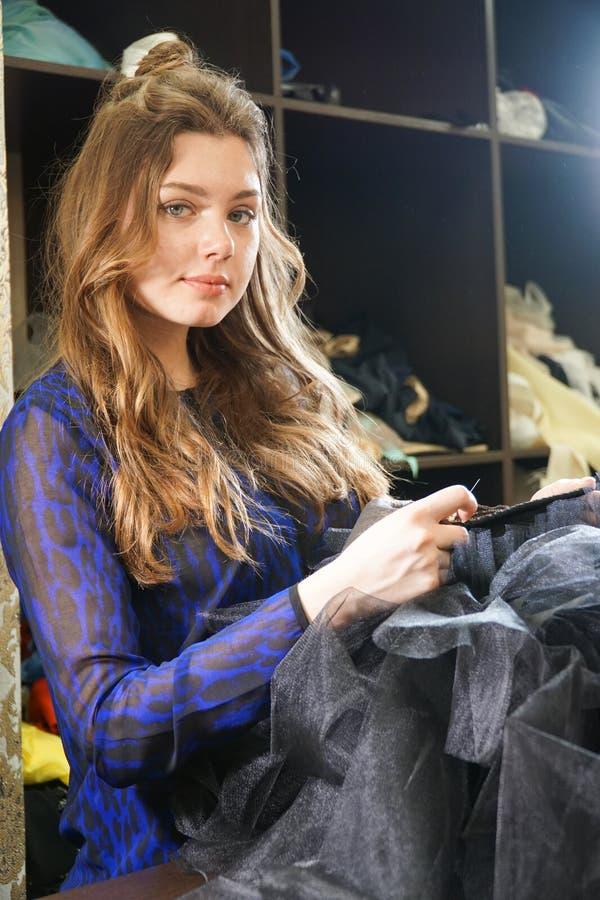 Het meisje is een naaister die in een naaiende workshop werken royalty-vrije stock foto's