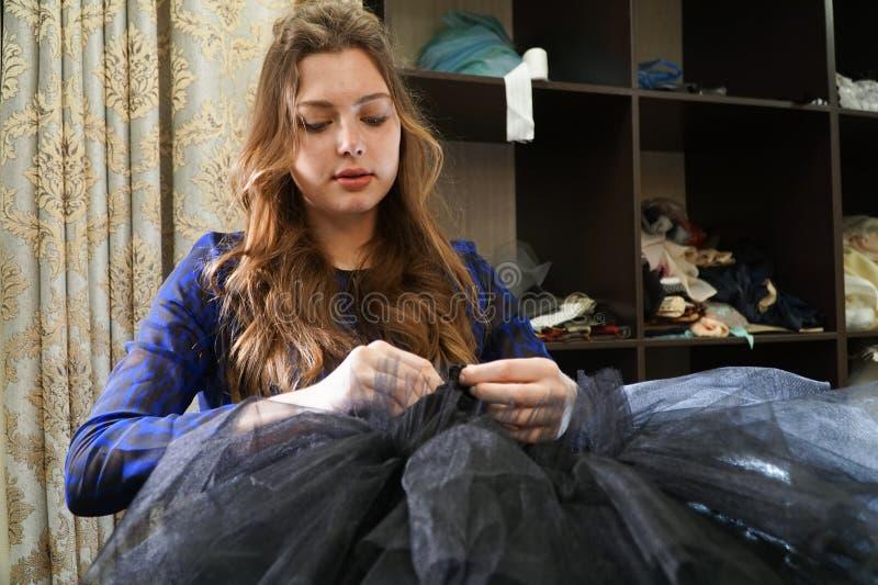 Het meisje is een naaister die in een naaiende workshop werken stock afbeeldingen