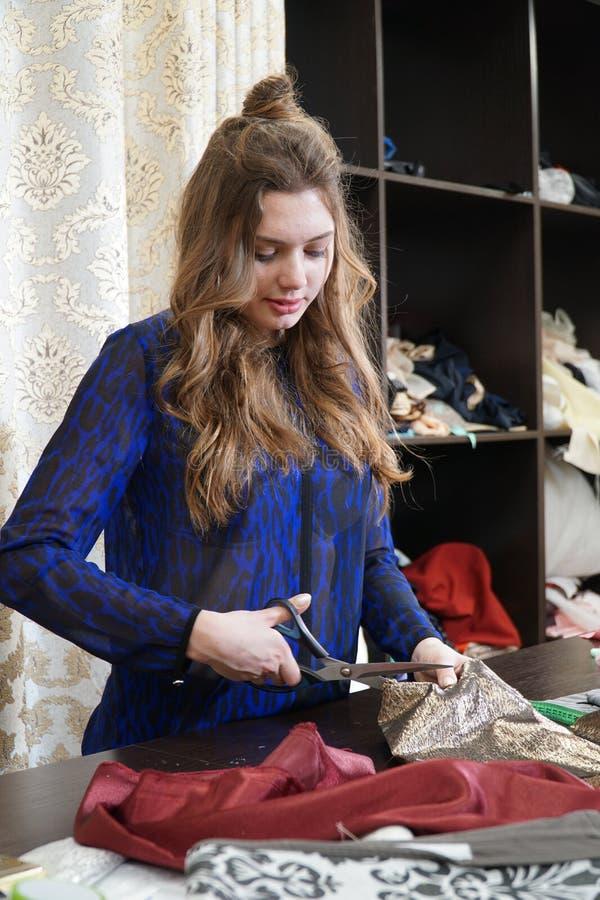 Het meisje is een naaister die in een naaiende workshop werken stock foto