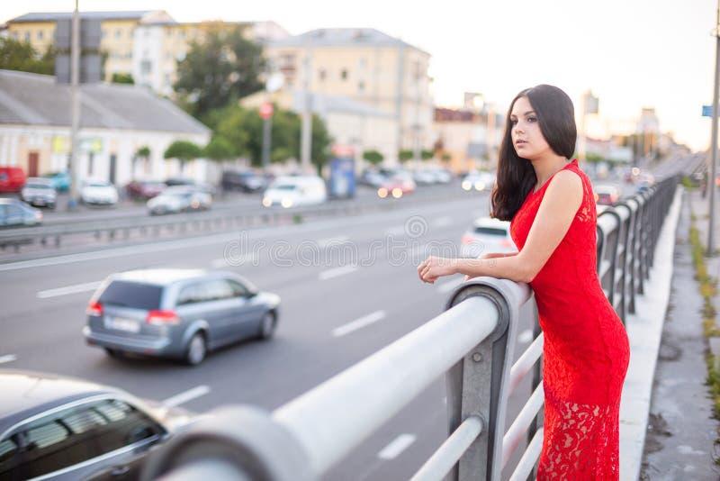 Het meisje in een rode kleding bevindt zich dichtbij de omheining van de rijweg royalty-vrije stock afbeelding