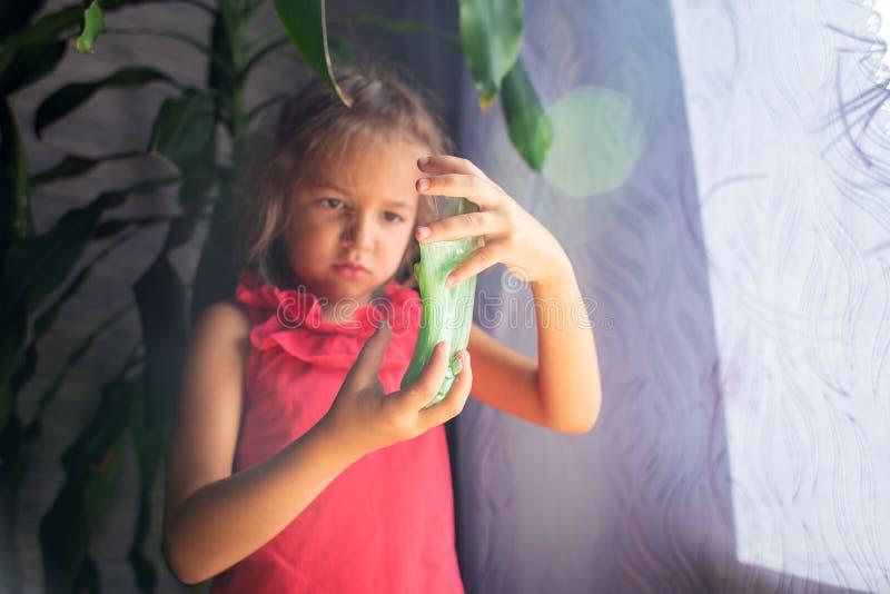 Het meisje in een rode onderhemdspelen met groen tegenover slijm stock foto's