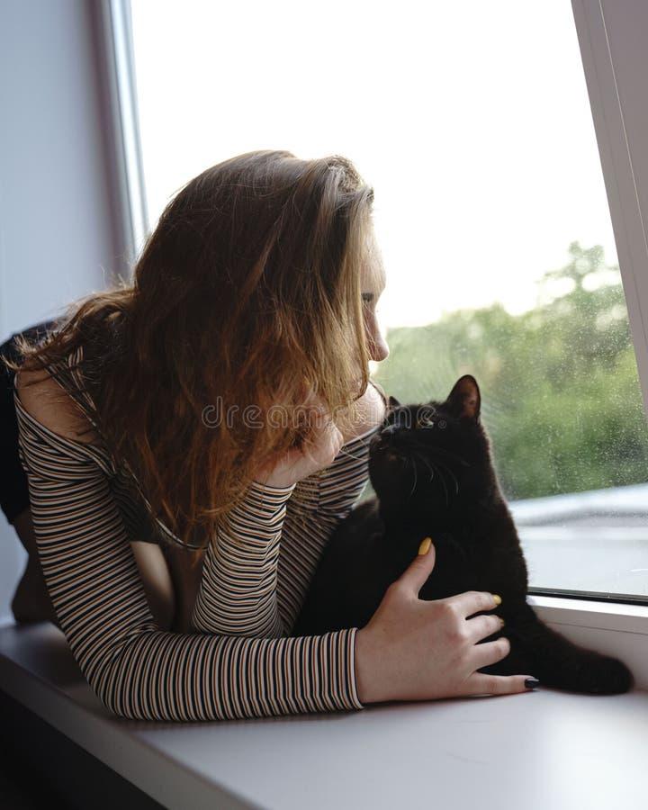 Het meisje in een rok en een kat zitten op het venster op de straatavond royalty-vrije stock foto's