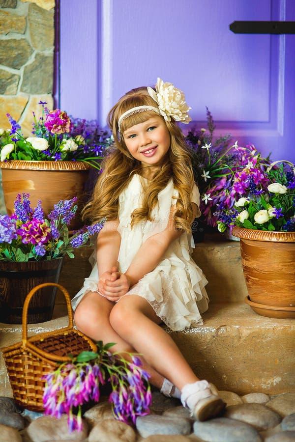 Het meisje in een roomkleding met lilac bloemen royalty-vrije stock afbeelding