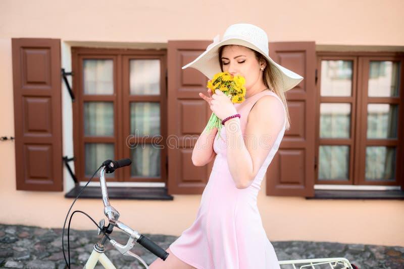 Het meisje in een roze kleding in een hoed op een fiets ruikt de geur van bloemen royalty-vrije stock foto's