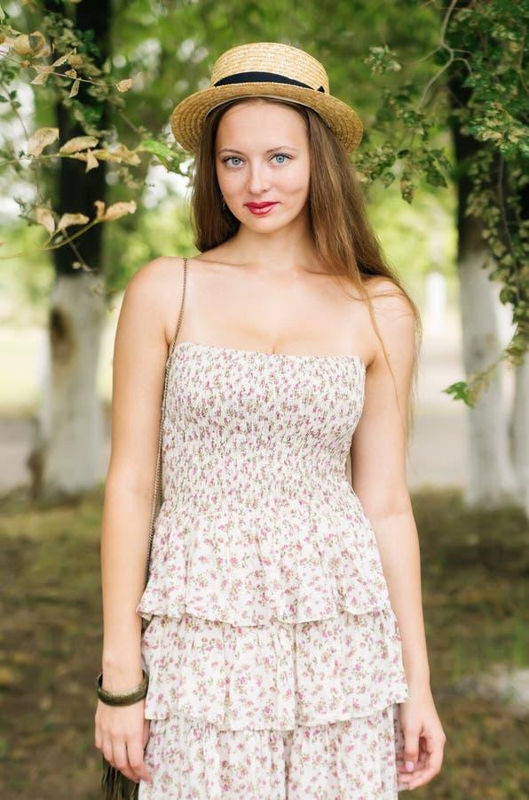 Het meisje in een strohoed en de zomer kleden het stellen in een stadspark royalty-vrije stock afbeeldingen