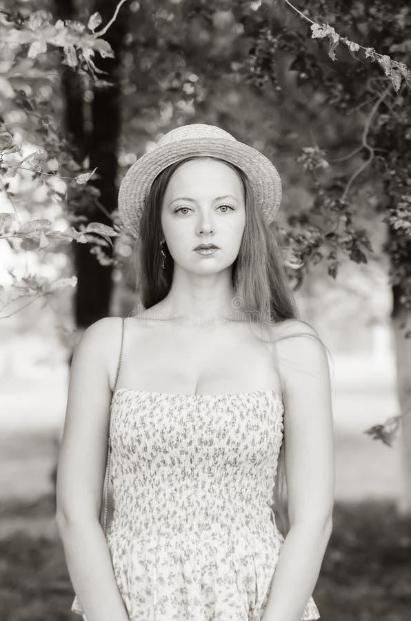Het meisje in een strohoed en de zomer kleden het stellen in een stadspark stock foto's
