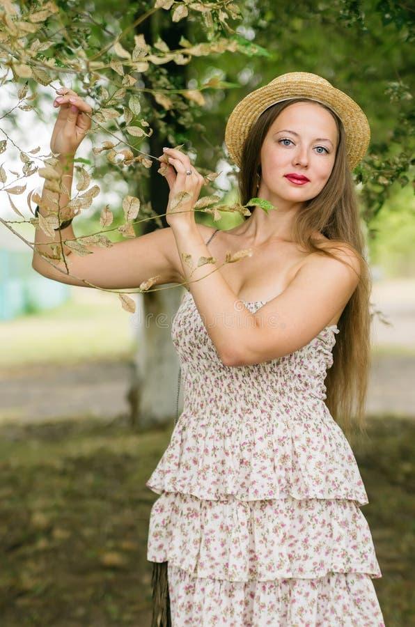 Het meisje in een strohoed en de zomer kleden het stellen in een stadspark stock afbeelding