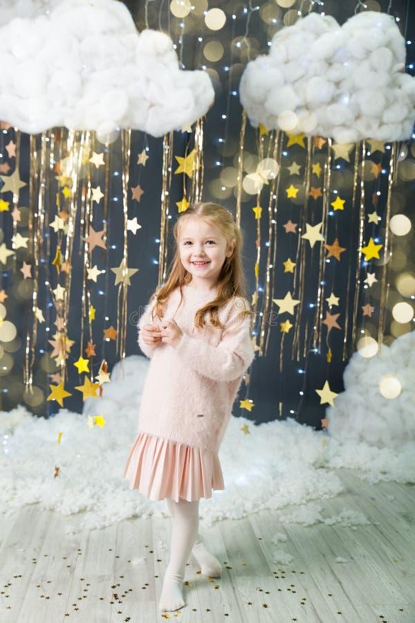 Het meisje in een studio met een goud speelt decor mee royalty-vrije stock afbeelding
