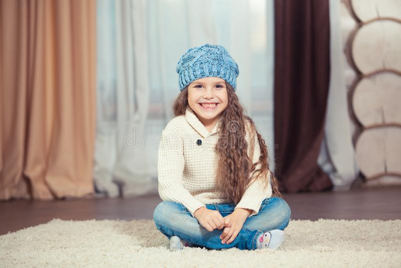 Het meisje in een sweater en een hoed zit op de vloer in een blokhuis, Kerstmis stock foto's