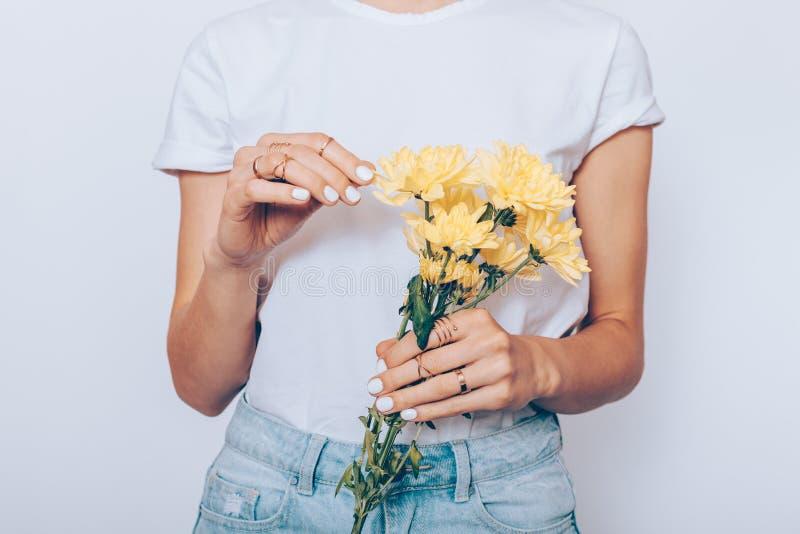 Het meisje in een T-shirt en jeans houdt een boeket stock fotografie