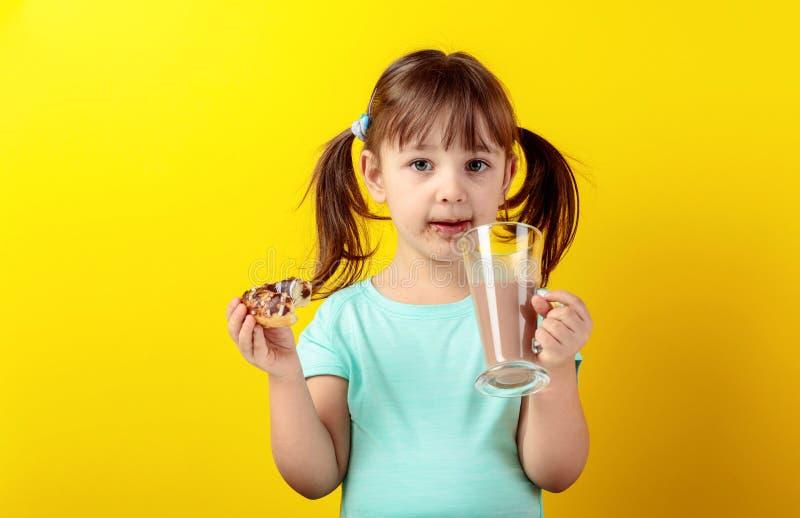 Het meisje in een turkooise t-shirt eet donuts en drinkt chocolademelk royalty-vrije stock fotografie