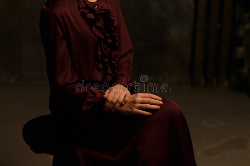 Het meisje in een uitstekende kleding zit op een stoel bescheidenheid zuiverheid kelderverdieping kerker royalty-vrije stock foto