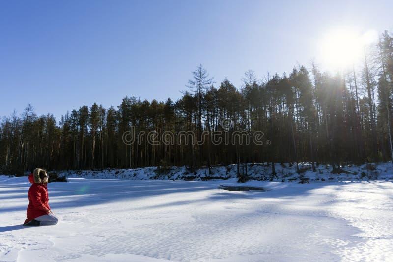 Het meisje in een warm rood jasje zit op het ijs van een de lenterivier en bekijkt de zon zich verheugt in de lente stock fotografie