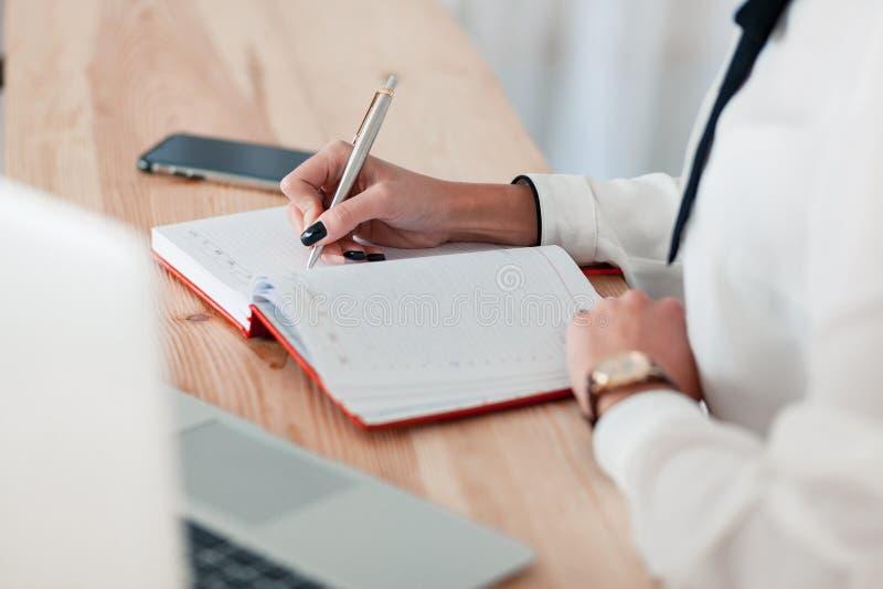 Het meisje in een witte blouse zit bij een lijst met laptop en schrijft in een rood notitieboekje stock fotografie
