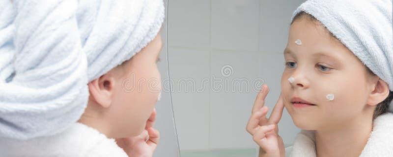 Het meisje in een witte laag met een handdoek op haar hoofd bevochtigt gezicht met een room voor een spiegel royalty-vrije stock afbeeldingen