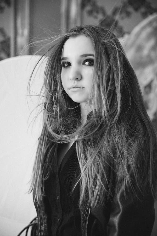 Het meisje in een zwart leerjasje een zwart-witte foto stock afbeelding