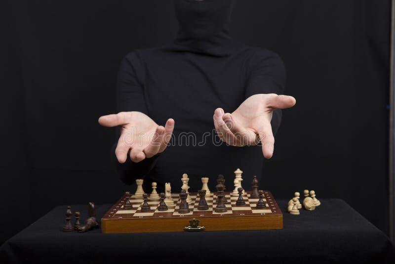 Het meisje in een zwarte blouse houdt handen op een houten schaakraad met royalty-vrije stock afbeelding