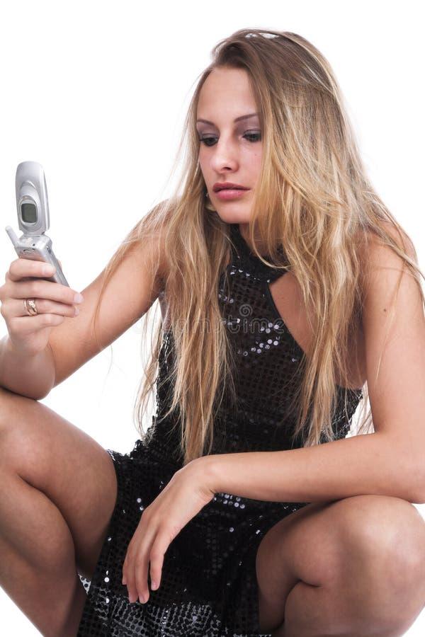 Het meisje in een zwarte kleding spreekt door de telefoon stock afbeelding