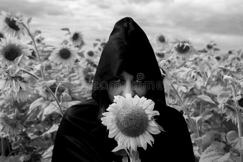 Het meisje in een zwarte mantel van dood tegen de achtergrond van zonnebloemen Concept Halloween stock afbeeldingen