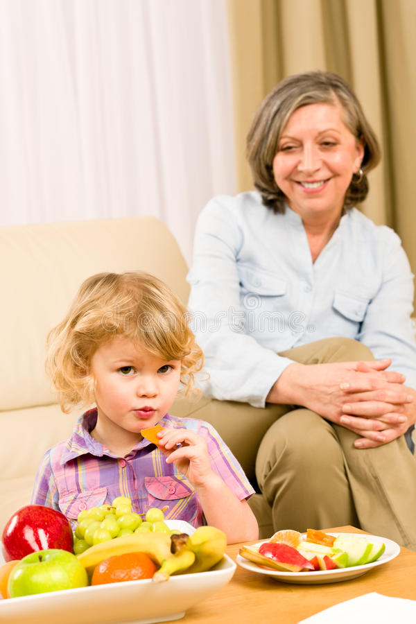 Het meisje eet abrikozenfruit met grootmoeder royalty-vrije stock afbeelding
