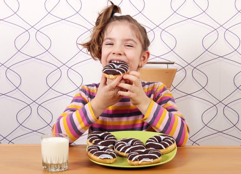 Het meisje eet chocolade donuts stock afbeeldingen
