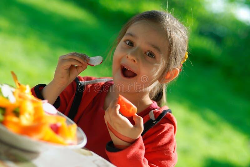 Het meisje eet een tomaat en een tuinradijs royalty-vrije stock foto