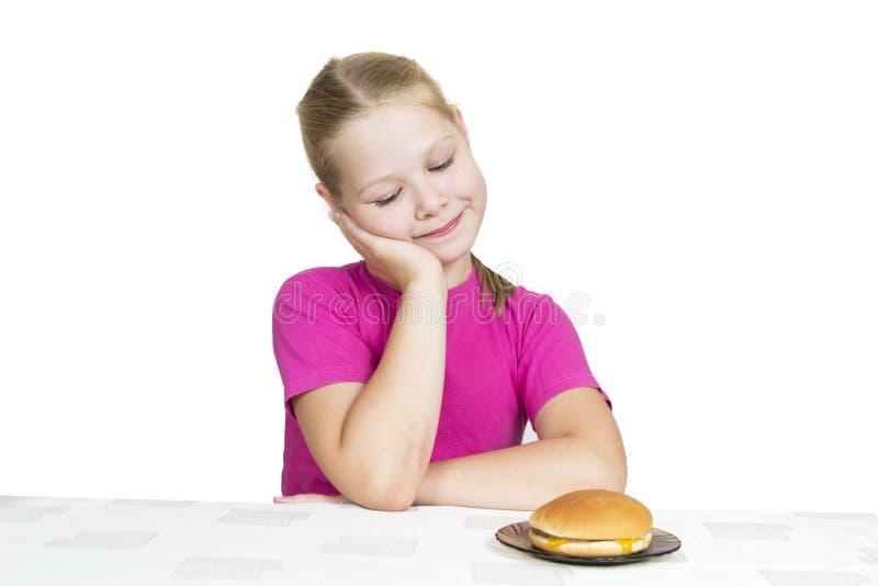Het meisje eet geïsoleerdk op het wit stock afbeelding