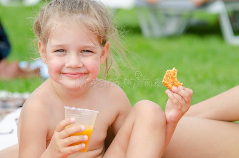 Het meisje eet koekjes, drinkt sap van plastic beschikbare kop en het glimlachen onderzocht het kader royalty-vrije stock afbeelding
