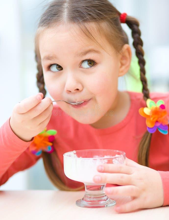 Het meisje eet roomijs in woonkamer royalty-vrije stock fotografie