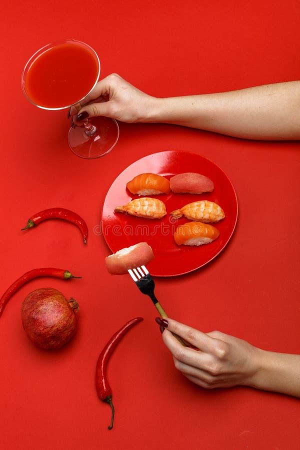 Het meisje eet sushi op een rode plaat Creatief concept restaurantlijst het plaatsen stock foto's