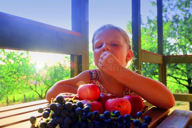 Het meisje eet vruchten Appelen en druiven op een lijst Het meisje zit bij een lijst aangaande een veranda en een eati royalty-vrije stock fotografie