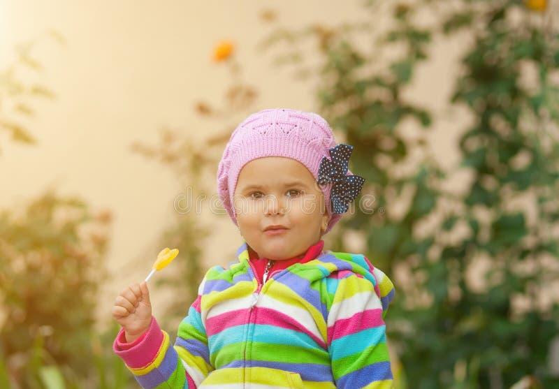 Het meisje eet zoet geel suikergoed royalty-vrije stock afbeeldingen