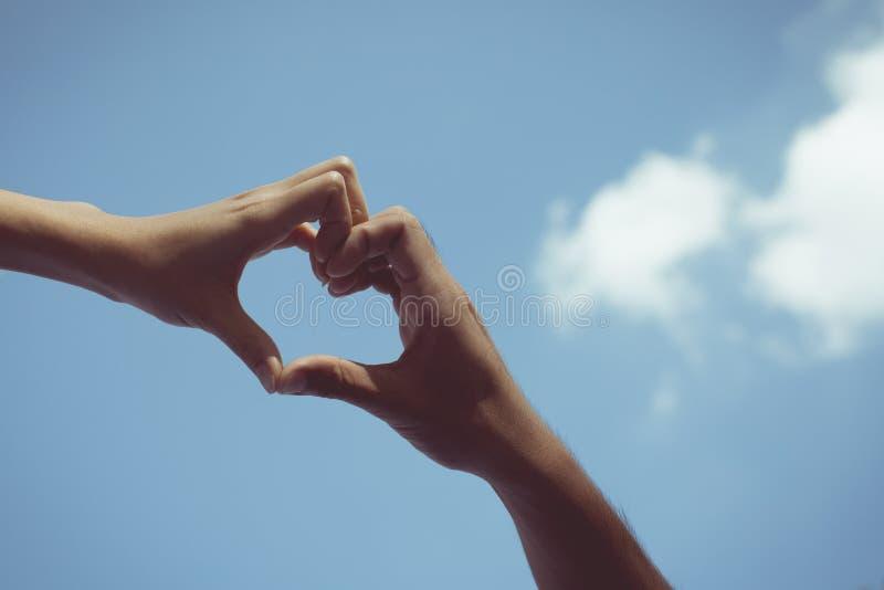 Het meisje en de jongen dienen de liefde blauwe hemel in van de hartvorm stock fotografie
