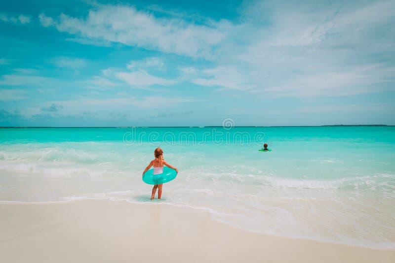 Het meisje en de jongen gaan zwemmen op strand stock foto's