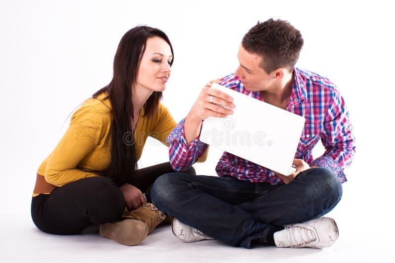 Het meisje en de jongen van de tiener met witte laptop stock afbeeldingen