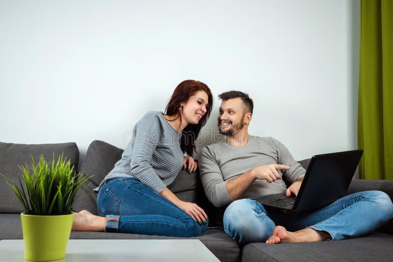 Het meisje en de kerel hebben pret in twee voor laptop Het concept familieverhoudingen, lettend op films die samen, tijd delen stock afbeelding