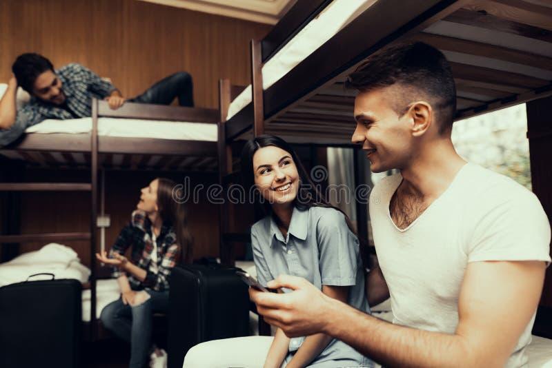 Het meisje en de Mens zitten op bedden en bekijken telefoon royalty-vrije stock fotografie