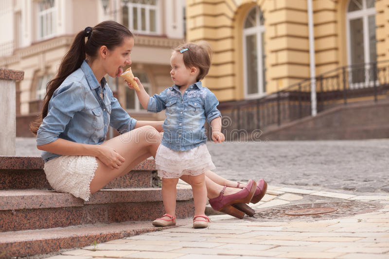 Het meisje en de moeder hebben pret met roomijs royalty-vrije stock afbeeldingen