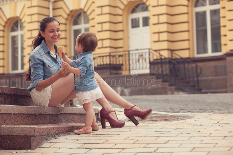 Het meisje en de moeder hebben pret met roomijs stock foto