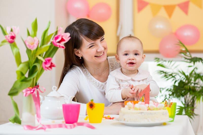 Het meisje van de baby met moeder viert eerste verjaardag stock fotografie