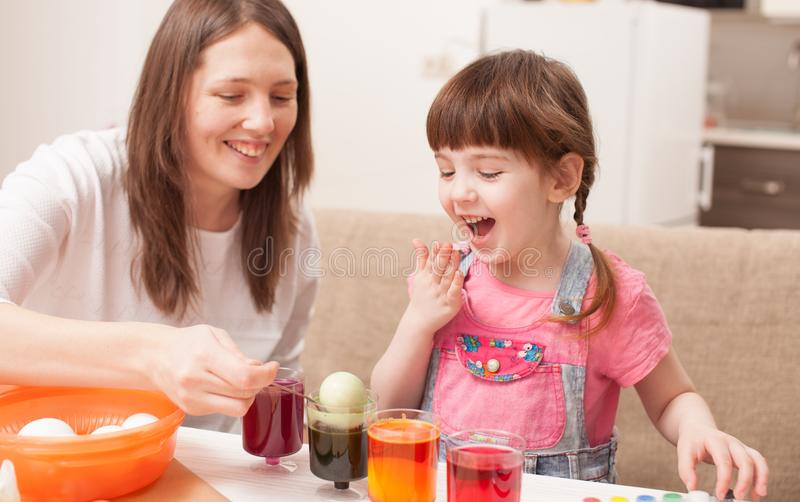 Het meisje en haar eieren van de moederverf thuis stock foto